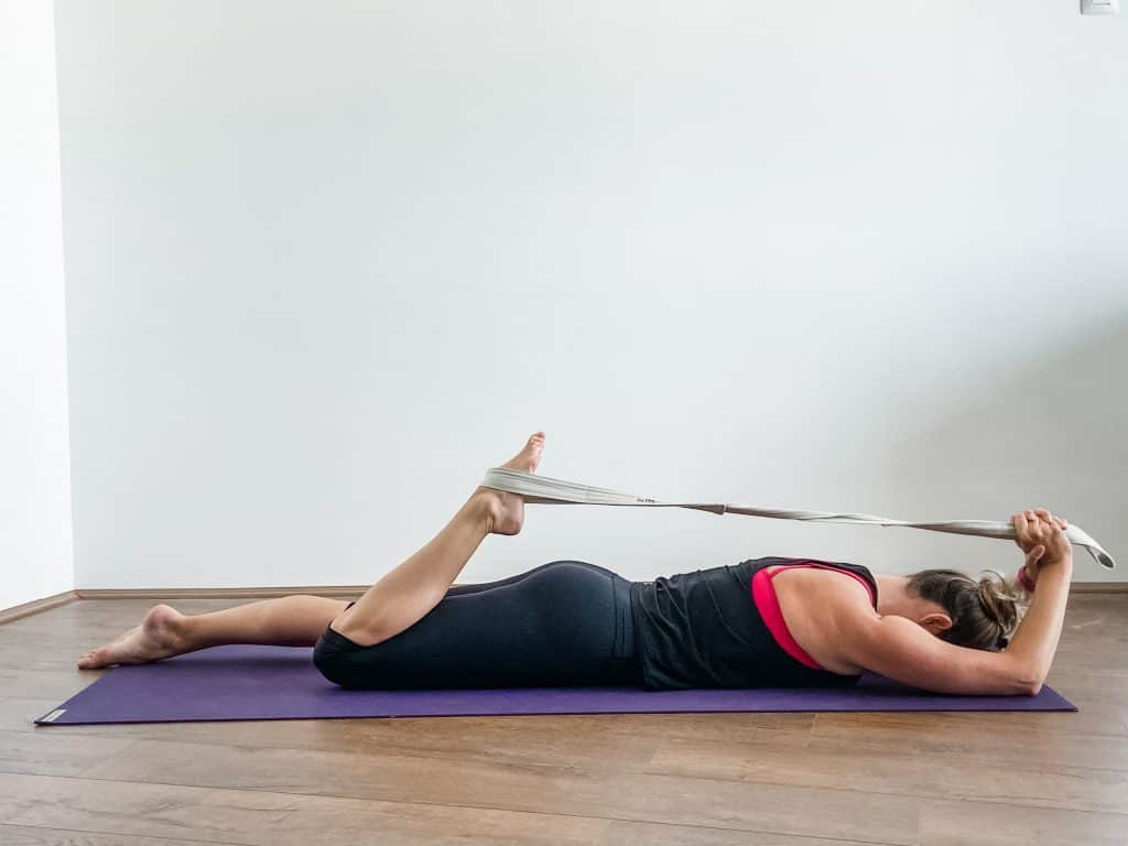 woman performing a prone quad stretch using a strap for modification - knee flexibility exercises.