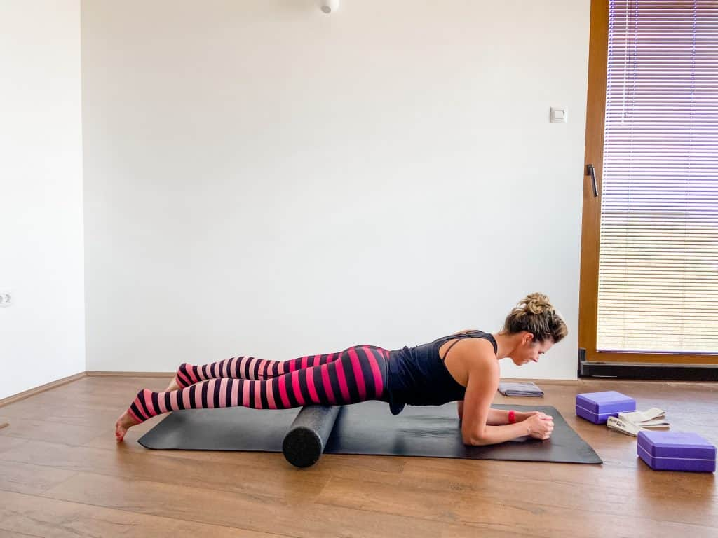 woman on a yoga mat demonstrating foam rolling for quads