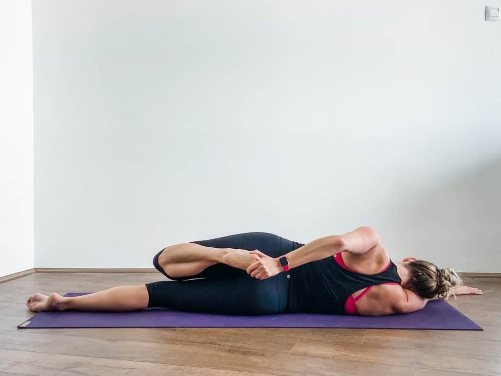 woman performing a side-lying quad stretch - knee flexibility exercises