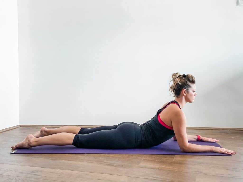 woman on a yoga mat doing sphinx pose, spinal extension flexibility exercise. prone on elbows, prone prop.