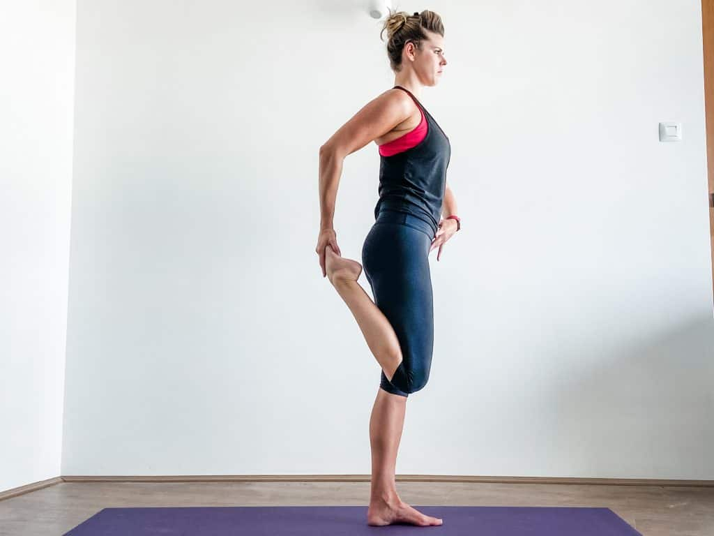 woman doing a standing quad stretch - knee flexibility exercises