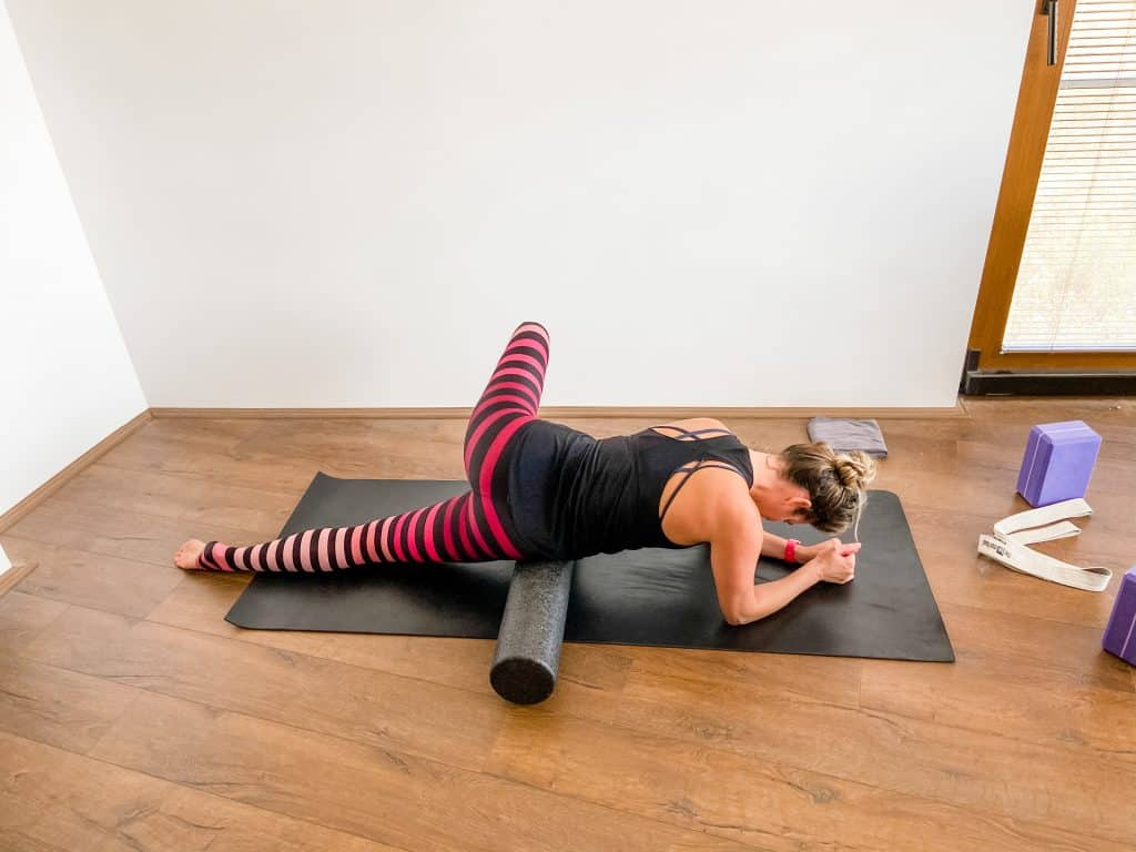 woman on a yoga mat demonstrating how to foam roll the TFL
