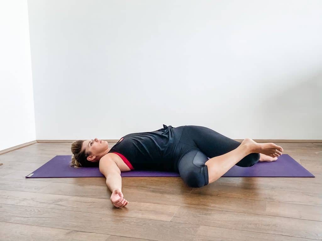 woman on a yoga mat demonstrating a TFL stretch