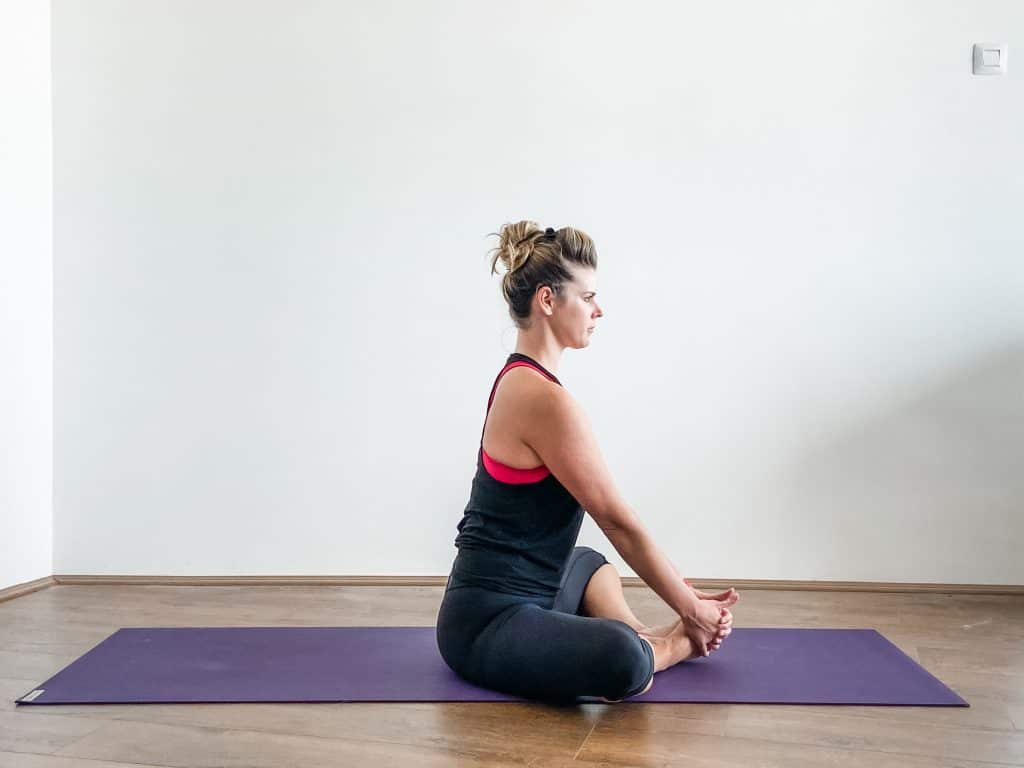 woman seated on a yoga mat in butterfly stretch (cobblers pose) for adductor stretching - hip flexibility exercises.