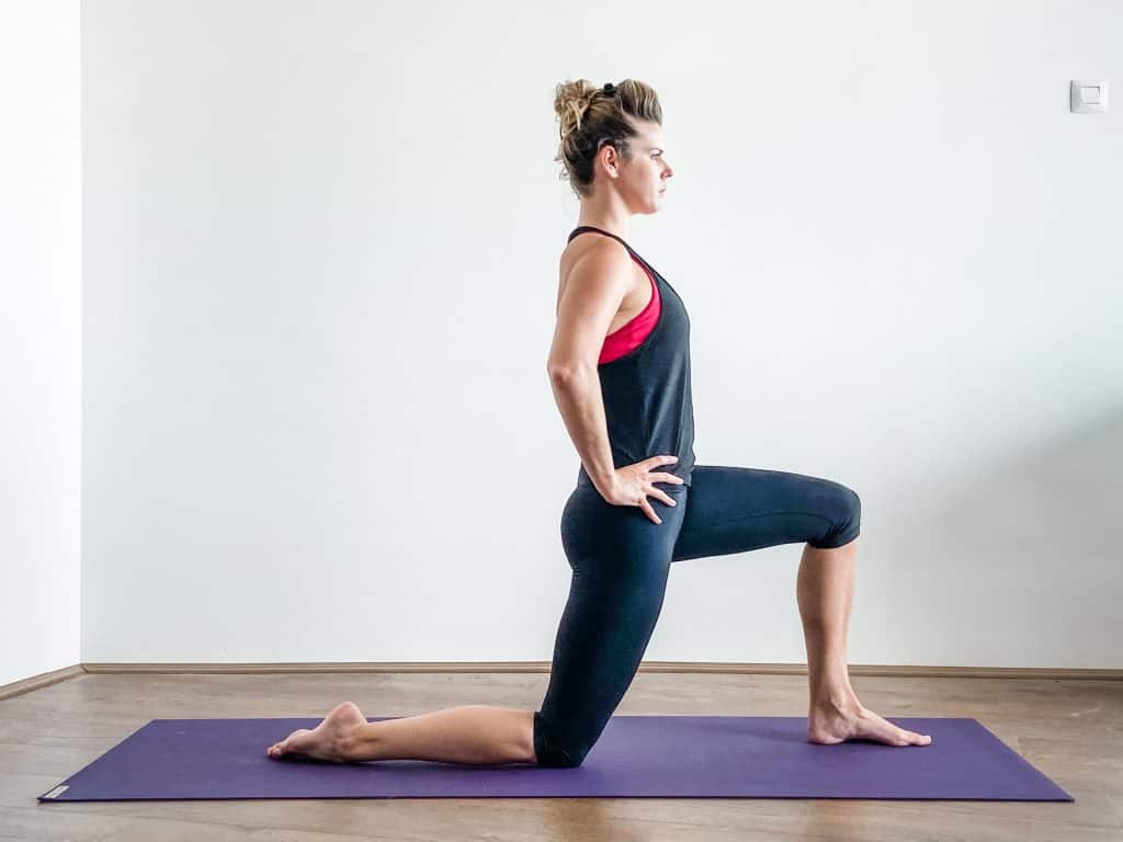 woman on a yoga mat demonstrating a kneeling hip flexor stretch