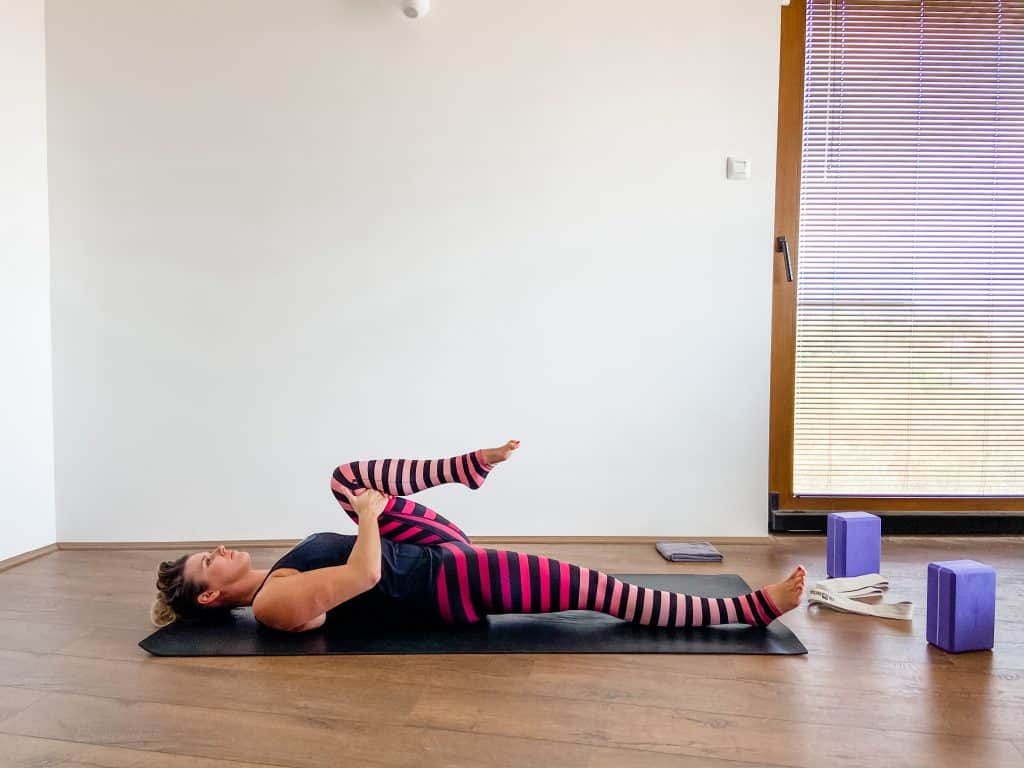 woman on a yoga mat performing a supine hip flexor stretch