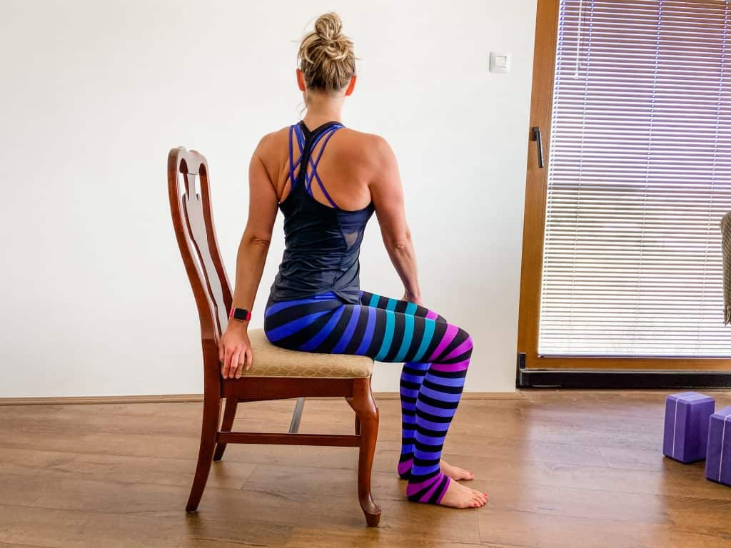 woman seated in a chair demonstrating a seated spinal twist stretch
