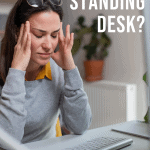 woman seated working at a desk in pain holding her head with text overlay do you need a standing desk?