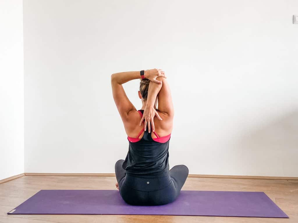 woman on a yoga mat demonstrating a triceps stretch