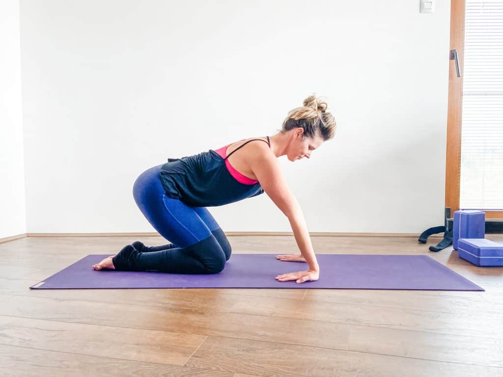 woman on a yoga mat demonstrating a wrist flexor stretch in quadruped