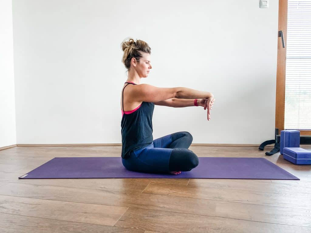 woman seated on a yoga mat demonstrating a wrist extensor stretch for elbow and wrist flexibility.