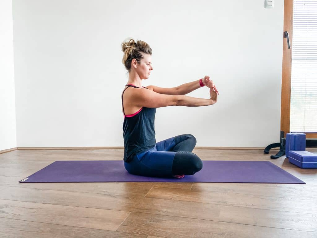 woman seated on a yoga mat demonstrating a wrist flexor stretch
