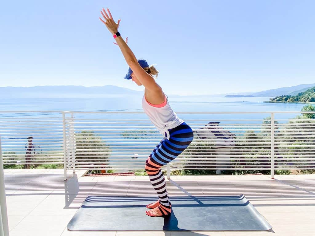 woman on a yoga mat outdoors doing chair pose wearing colorful striped leggings in an article about creative gifts for fitness lovers