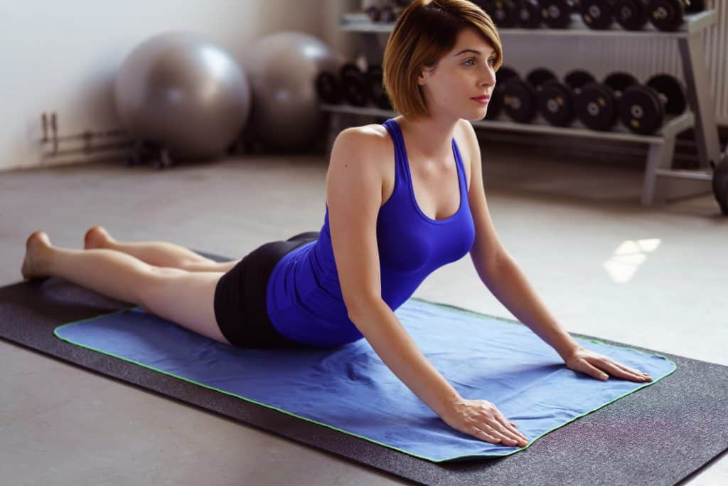 woman on a yoga mat performing cobra pose for spinal extension mobility and flexibility