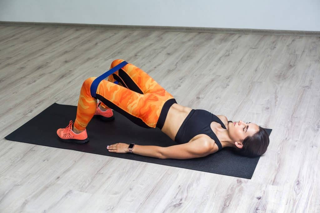 a woman lying on a gym mat in bridge pose demonstrating a core/hip stability exercise