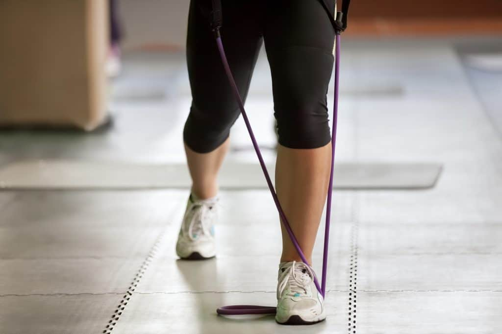 woman using a resistance band at home
